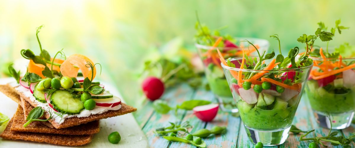 Variety of healthy appetizer: toasts and salads with fresh vegetables